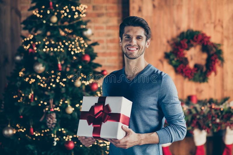 Photo of cheerful positive handsome man smiling toothily holding wrapped gift box present from santa claus standing in stock photography