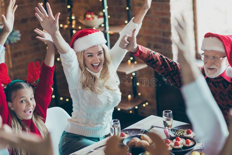 Photo of cheerful positive nice pretty woman with daughter nearby with grandfather in santa hat headwear at table with royalty free stock images