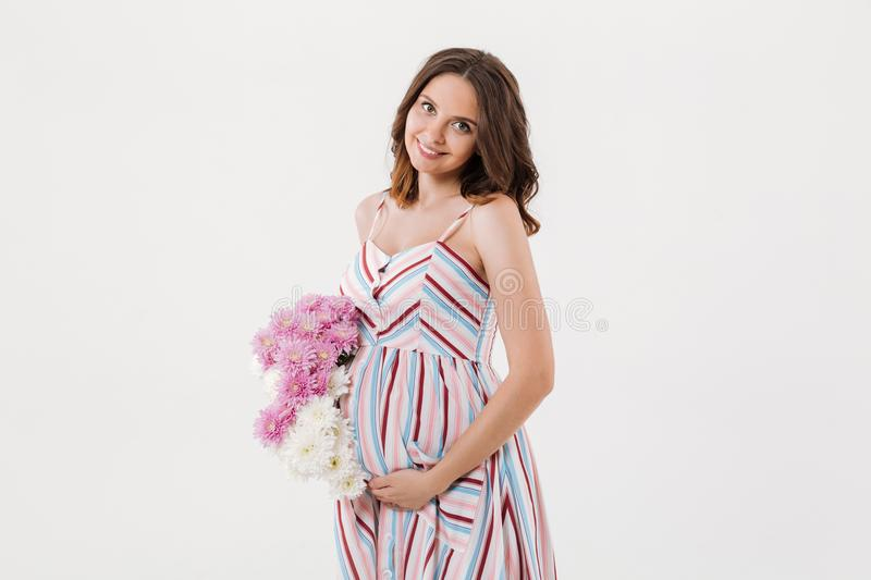 Cheerful pregnant woman holding flowers. royalty free stock image
