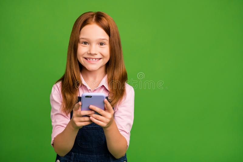 Photo of cheerful pretty little schoolchild holding telephone hands texting with classmates friends wear denim overall. Photo of cheerful pretty little stock photo