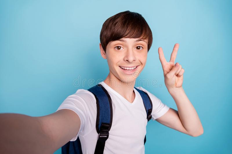 Photo of cheerful rejoicing overjoyed nice boy taking selfie showing v-sign on his way home while isolated with blue royalty free stock photo