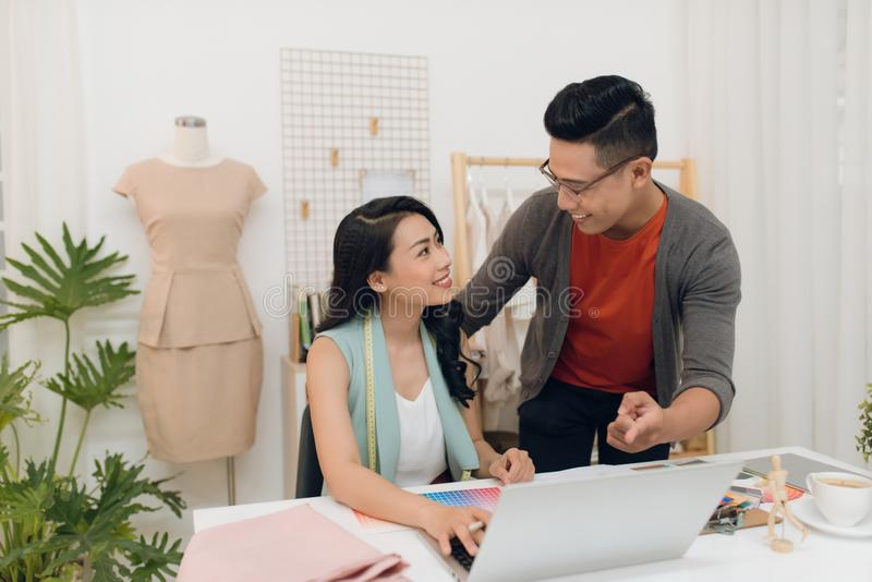 Photo of cheerful woman and man designers working in the studio stock photography