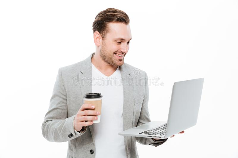 Cheerful young businessman drinking coffee using laptop stock photos