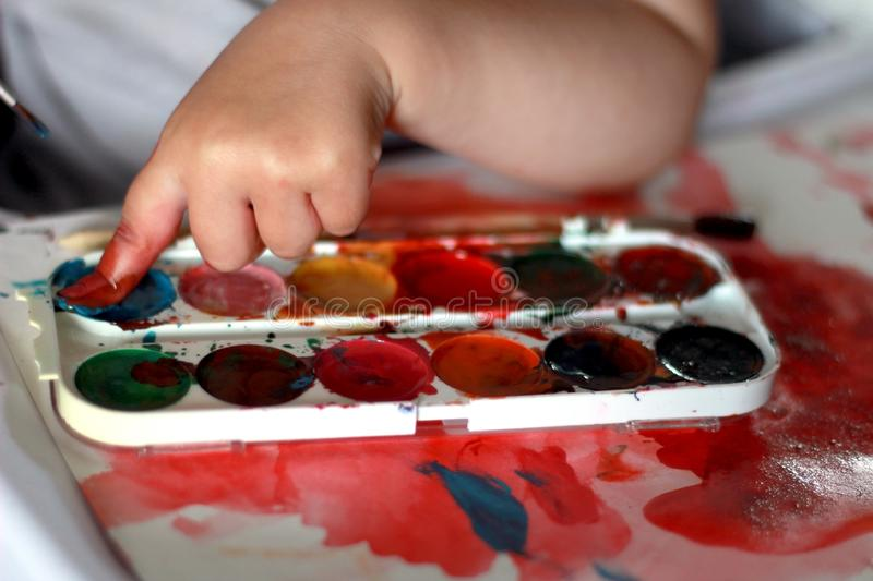 Photo child draws touches the finger with watercolor honey paint stock photo