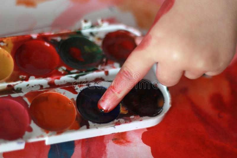 Photo child draws touches the finger with watercolor honey paint royalty free stock images
