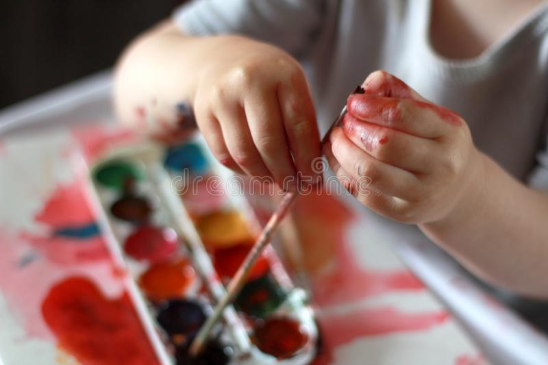 Photo child touches the brush with dirty hands in the paint. against a watercolor paint background stock photography