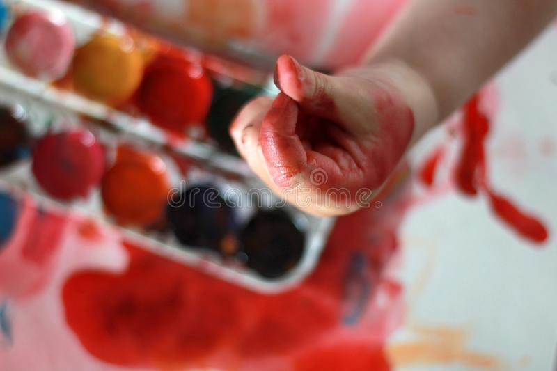 Photo child touches the paint in his hands. hands in paint. against a watercolor paint background royalty free stock photo