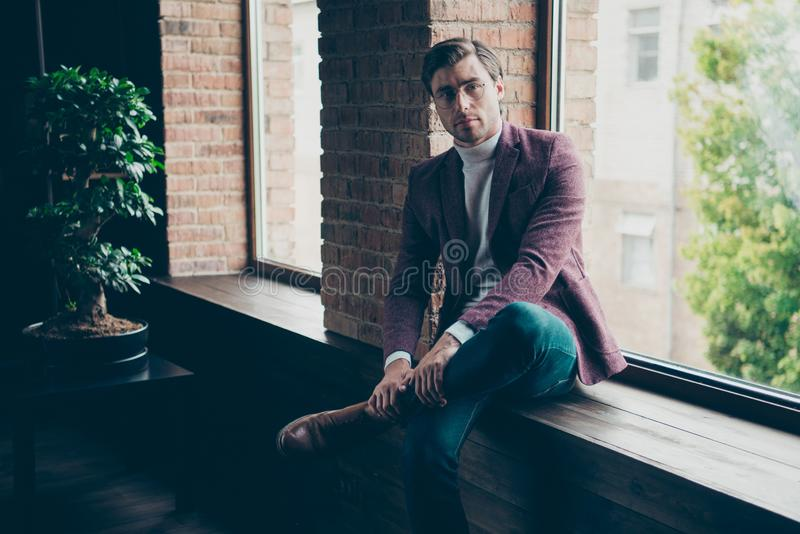 Photo of classy business guy looking clever eyes on camera sitting window sill wear specs stylish blazer turtleneck and royalty free stock image