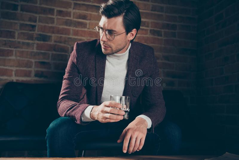 Photo of classy macho business guy holding alcohol looking side thinking about new startup wear specs stylish blazer royalty free stock image
