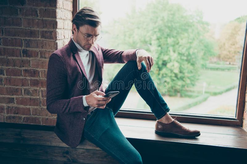 Photo of classy macho business guy looking telephone sitting side on window sill search new workers online wear stylish royalty free stock photo