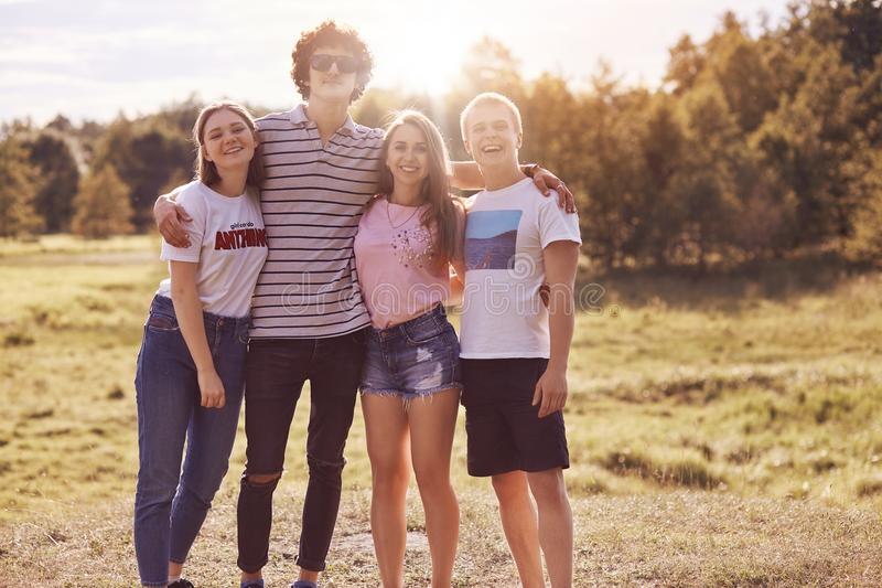 Photo of close friends stand outdoor, have picnic together, embrace and smile happily at camera, have good relationship, dressed i royalty free stock photos