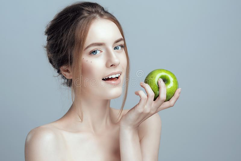 Photo of a close-up of a beautiful girl with a green apple in her hand. She has clean and even skin. royalty free stock photo