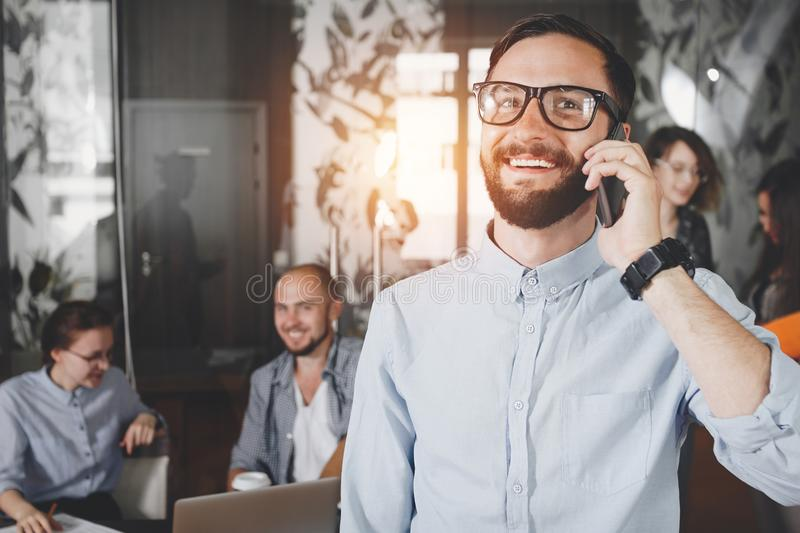 Photo close-up young smiling bearded businessman in glasses speaking on smartphone on background coworking meeting business team. stock image
