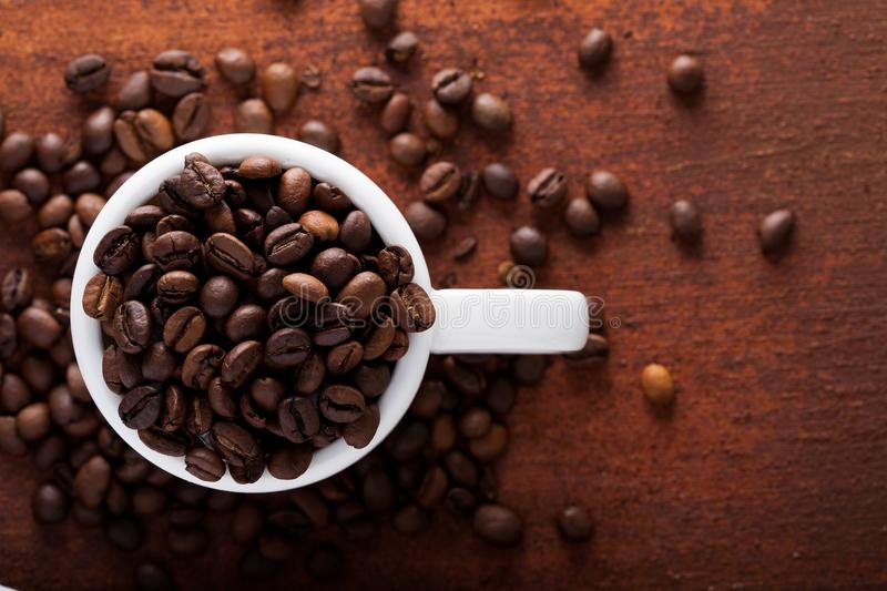 Photo closeup of coffee beans in white cup. Rusty background. royalty free stock photo