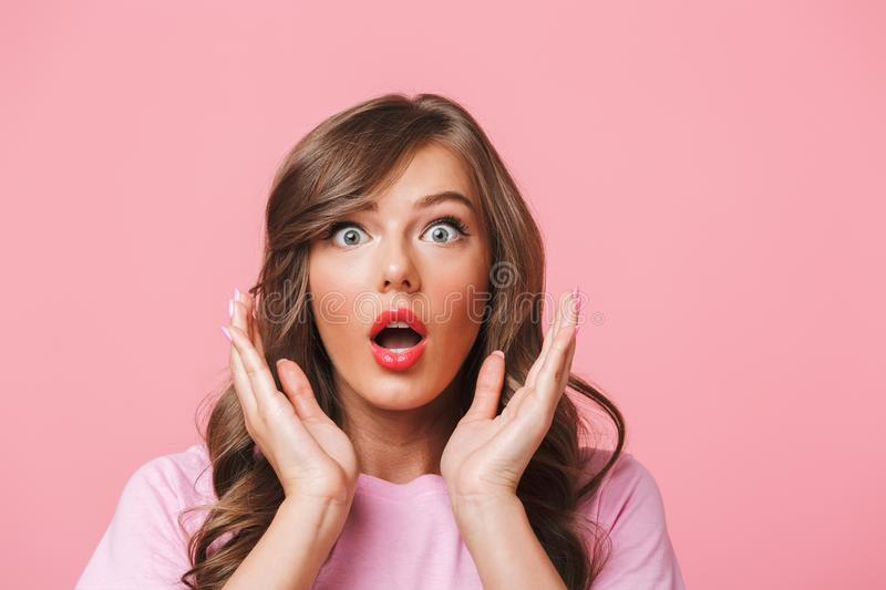 Photo closeup of scared woman with long curly hair in basic t-shirt bulging eyes and raising hands in fear or panic, isolated stock photography