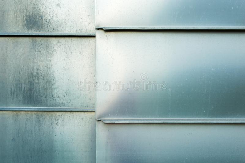 Photo closeup shiny steel aluminum fragment of protective facade structure made of metal plates sheets horizontally assembled royalty free stock images