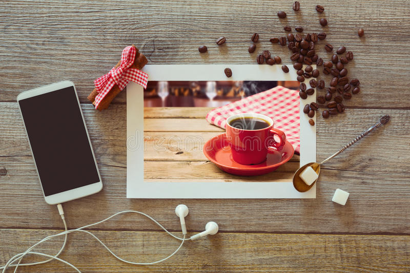 Photo of coffee cup on wooden table with smart phone and coffee beans. View from above royalty free stock photography