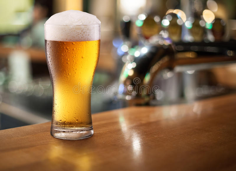 Photo of cold beer glass on a bar. Closeup stock image