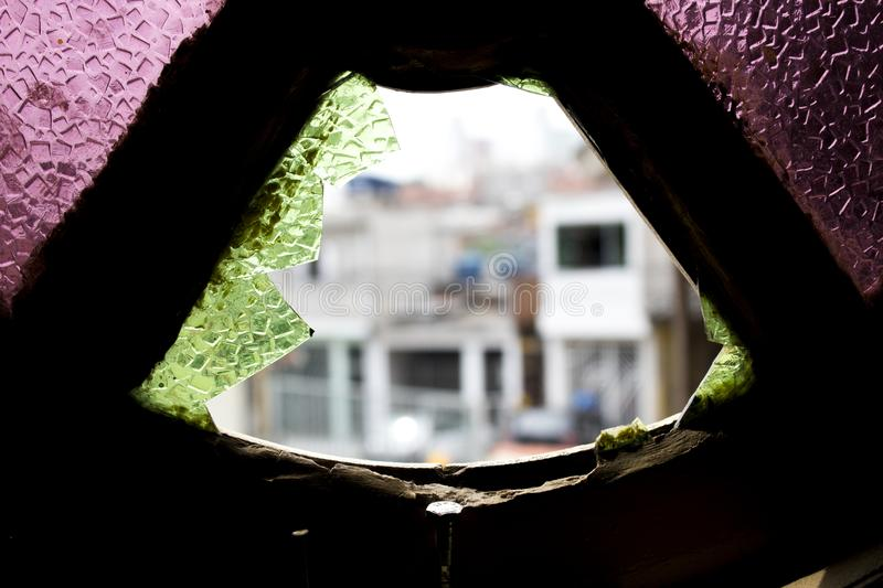 Photo of a colored window broken by a stone. Hole in the window glass broken by a stone. Pieces of glass hanging around the hole, urban photography blurred by stock image