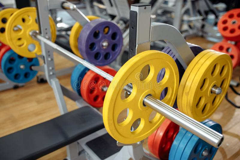 Photo of colorful weight bench with barbell in gym. sport, Fitness and bodybuilding concept. royalty free stock image