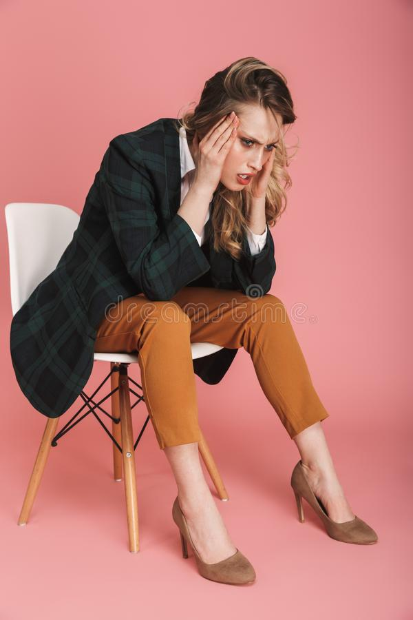 Photo of concentrated businesswoman sitting in chair and grabbing head isolated over pink background. Photo of concentrated businesswoman wearing jacket sitting stock photography