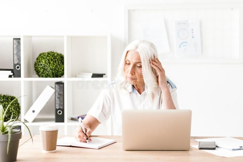 Concentrated mature woman with laptop computer stock photos
