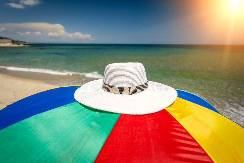 Photo conceptuelle de chapeau se trouvant sur le parapluie coloré au bord de la mer photographie stock libre de droits