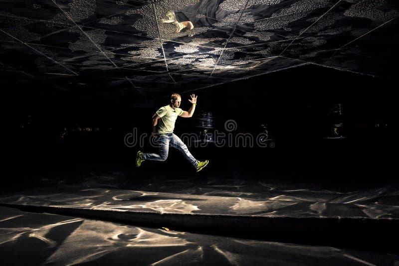 Photo conceptuelle de jeune et attirant homme dans le saut sur le fond noir photo stock