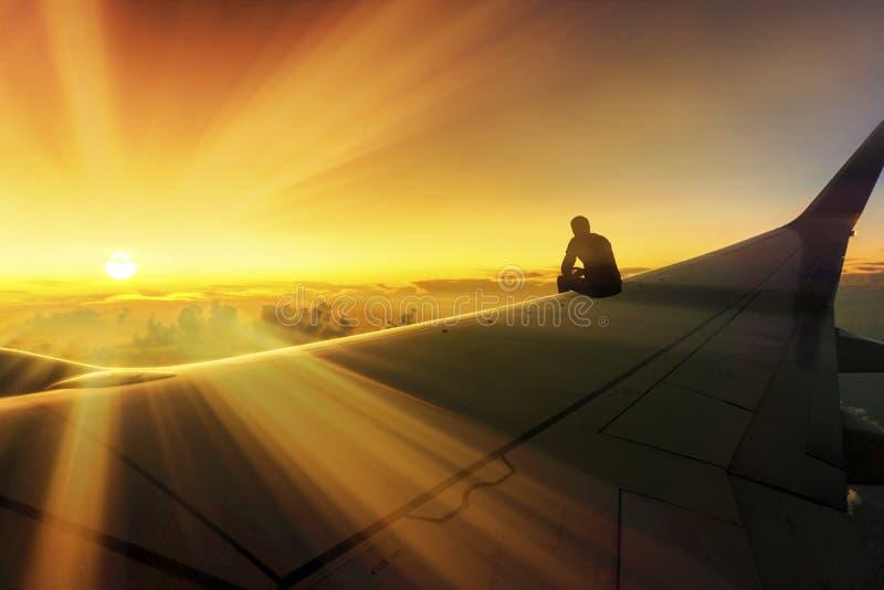 Photo conceptuelle de voyage d'aventure de la silhouette de l'homme se reposant sur la destination de Wing Watching Stunning Suns photo libre de droits