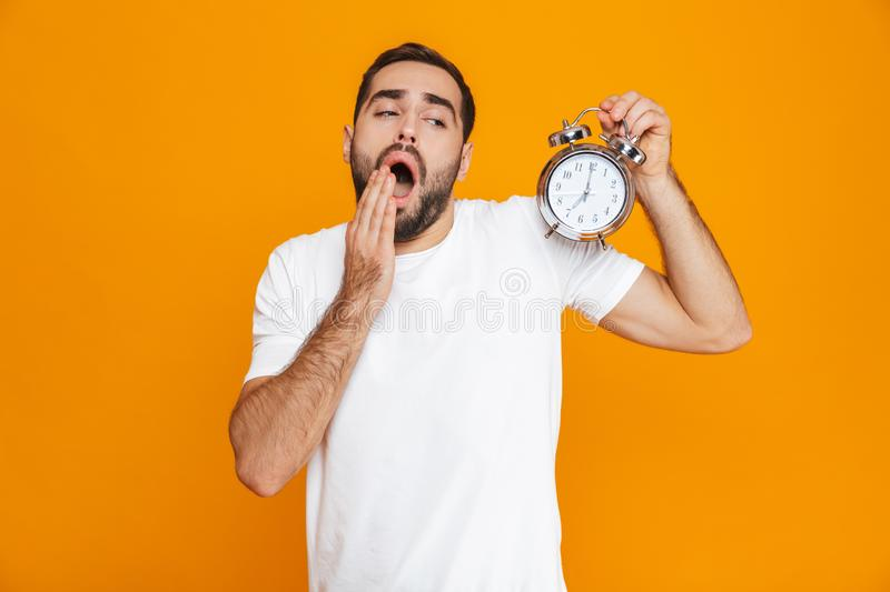 Photo of concerned man 30s in casual wear holding alarm clock, isolated over yellow background stock photography