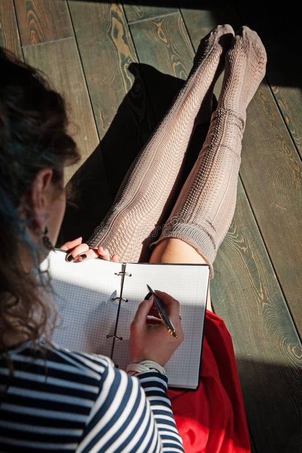 Photo confortable de l'écriture de jeune femme dans le carnet se reposant sur le flo photos libres de droits