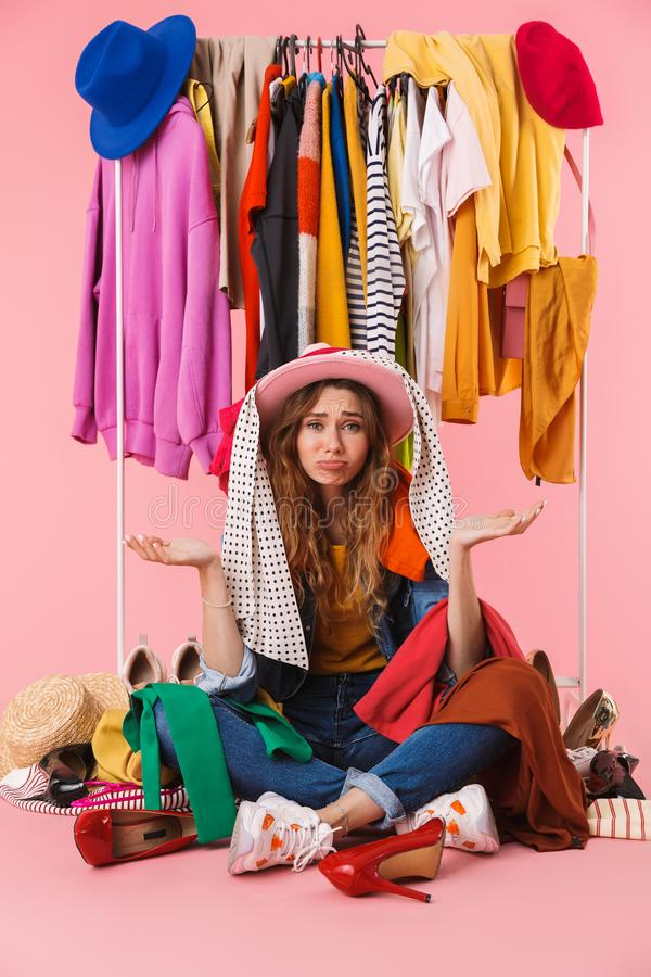 Photo of confused young woman wearing hat sitting near bunch of clothes stock photo