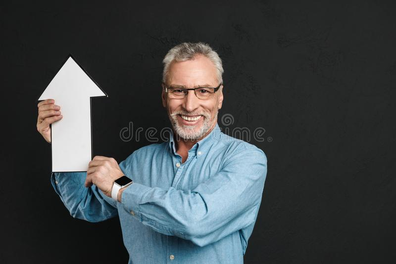 Photo of content elderly man 60s with grey hair and beard wearing glasses holding blank speech arrow pointer directing upward, is. Photo of content elderly man royalty free stock images