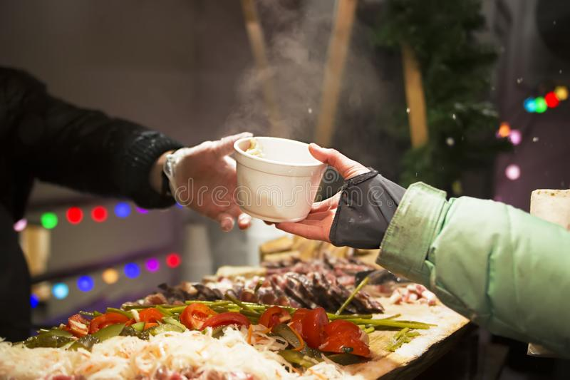 The cook pours the broth into the cups. Cooking food on the street royalty free stock images