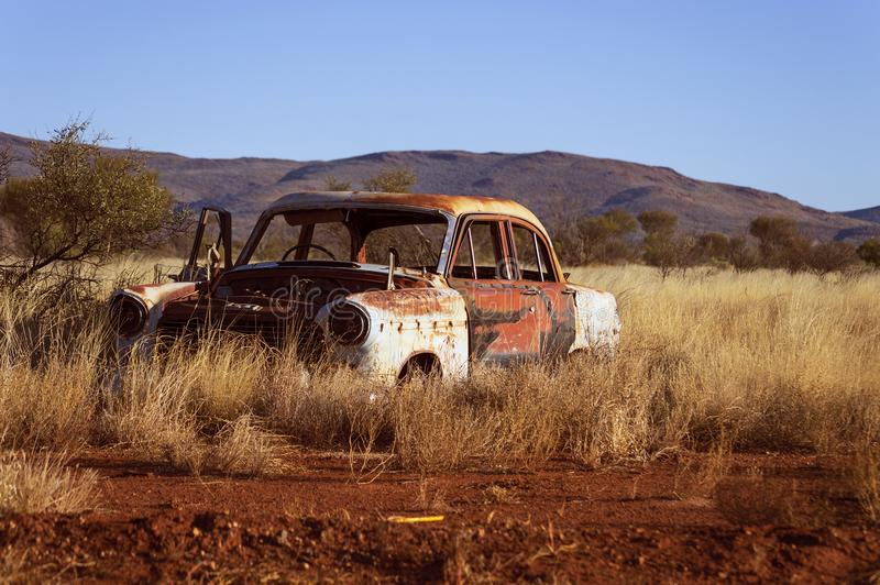 Photo of Corroded Vintage White and Red Sedan on Brown Grass royalty free stock photo