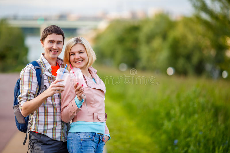 Photo of couple - man and woman with milkshakes. Photo of couple - men and women with milkshakes in park at summer royalty free stock images