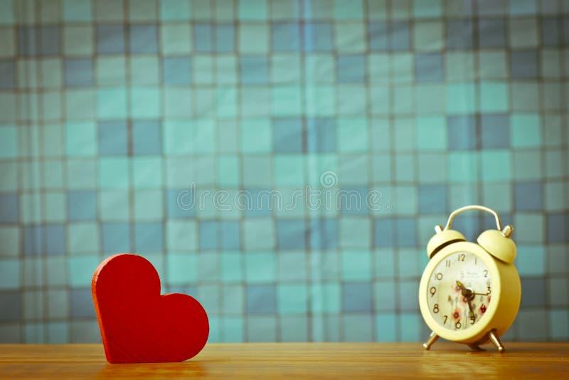Photo courante : Coeur en bois rouge sur un fond en bois avec le boke b photos stock