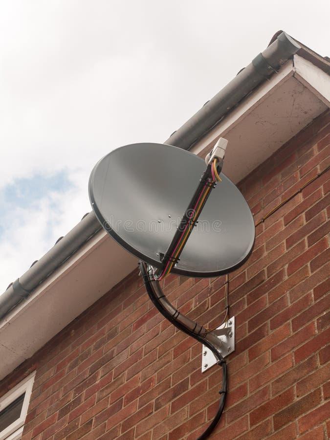Photo courante - un satellite noir de plat de ciel étroit sur le mur de briques photos stock