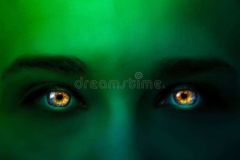 Photo créative du visage d'une femme avec le gradient vert clair au néon et de rougeoyer dans les yeux multicolores foncés avec u image libre de droits