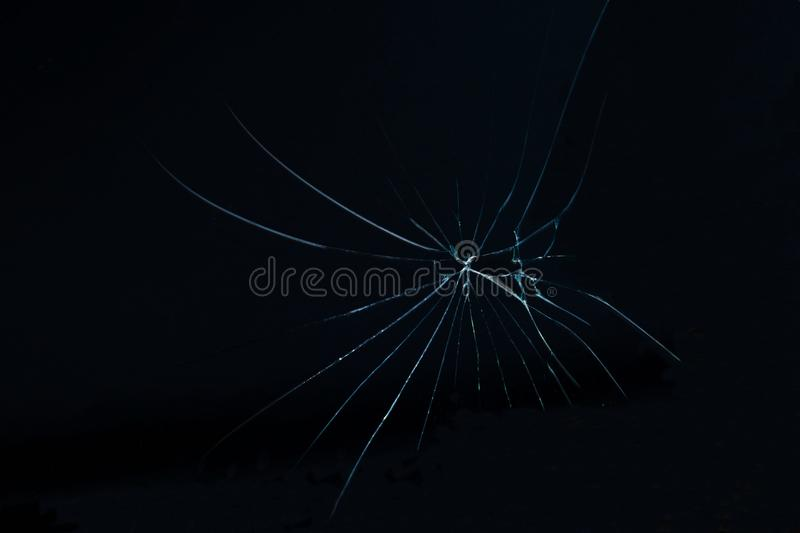 Crack on the glass on a black background. Photo of cracked broken glass on a black background using a macro lens royalty free stock photography