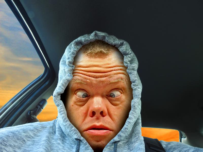 Hoodie cross eyed driver. Photo of a cross eyed hoodie driver looking confused and tired as he has been driving all night stock photos