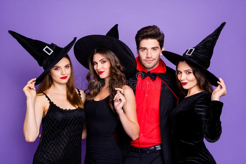 Photo of cruel witch ladies and warlock guy ready for halloween student event wear black dresses hats and vampire cloak. Photo of cruel witch ladies and warlock stock images
