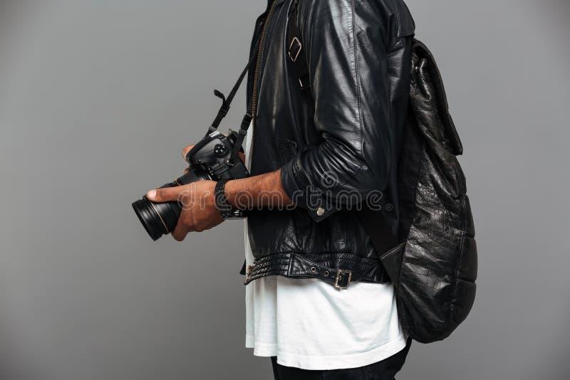 Photo cultivée d'homme africain élégant avec le sac à dos tenant la photo photos stock