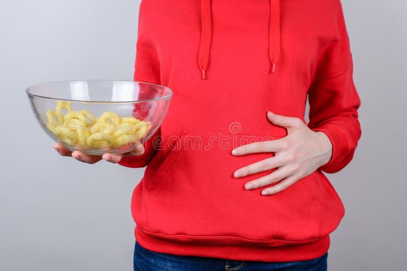 Photo cultivée de plan rapproché des personnes de personne dans le pull lumineux de jeans tenant les anneaux d'oignon presque vid images libres de droits
