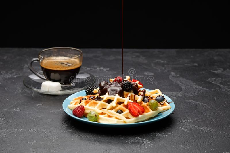 Photo of cup of black coffee with sugar with Viennese waffles with strawberries, raspberries, gooseberries and chocolate. On empty black background royalty free stock photos