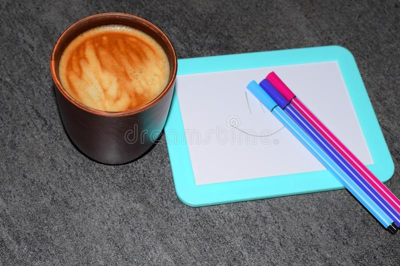 Photo of a cup of coffee on a background of a magnetic board and felt-tip pens. A saturated coffee color with an airy foam and a b. Background photo of colored stock photo