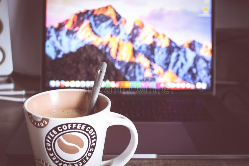 Photo of Cup of Coffee in Front of the Laptop stock photography