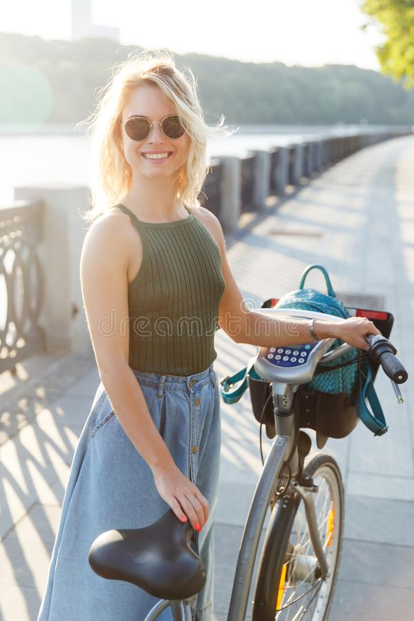 Photo of curly blonde in denim skirt standing next to bike on bridge in city stock image