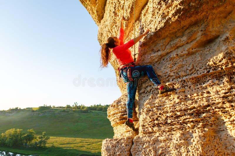 Photo of curly-haired climber girl climbing rock stock photos