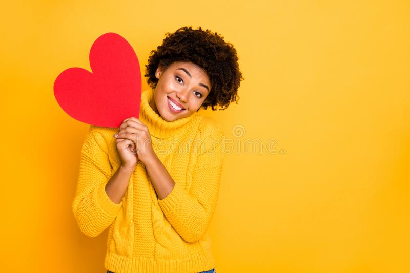 Photo of cute charming nice sweet attractive black curly girlfriend wearing yellow sweater holding big red heart with. Photo of cute charming nice sweet royalty free stock image